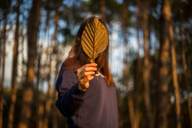 Woman covering face with leaf in forest during sunset