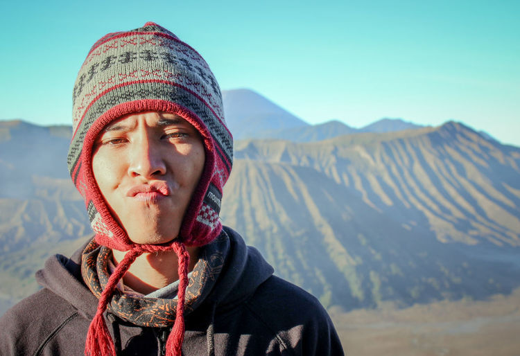 Portrait of young man standing against mountains during winter