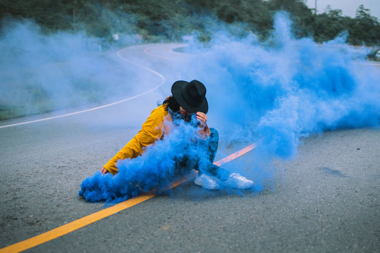 Woman sitting with blue distress flare on road