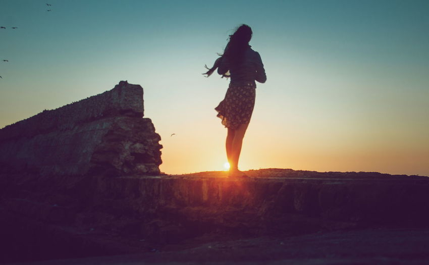 Woman standing on mountain during sunset