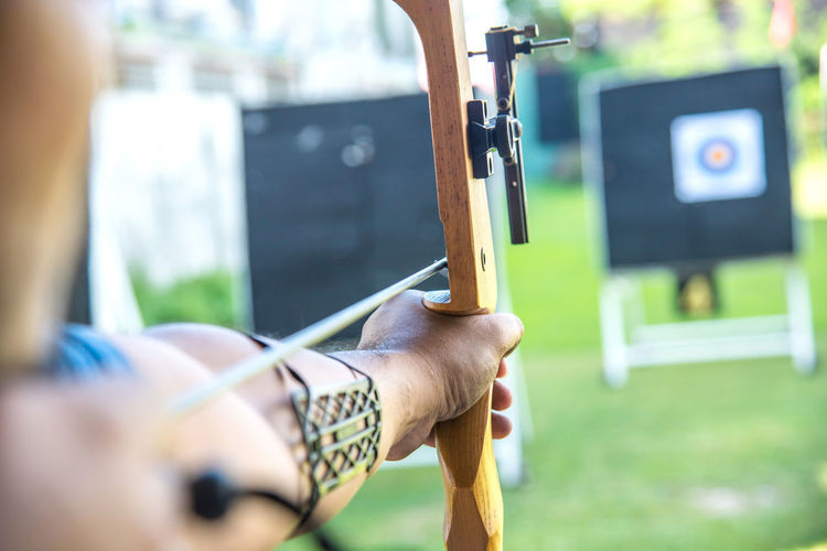 Accuracy Adult Aiming Arrow - Bow And Arrow Day Focus On Foreground Hand Headshot Holding Human Hand Leisure Activity Lifestyles Men One Person Outdoors Real People Selective Focus Skill  Sports Target Young Adult