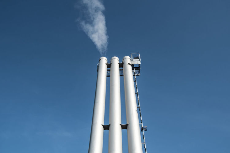 Blue Built Structure Clear Sky Day Emitting Factory Industry Low Angle View No People Outdoors Power Station Sky Smoke - Physical Structure Smoke Stack Technology Vapor Trail