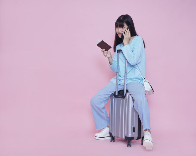 Woman using phone while sitting against pink background