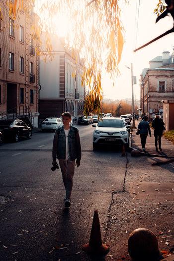 Man on city street against sky during sunset