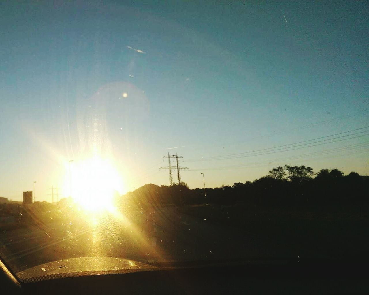 sun, car, vehicle interior, lens flare, sky, transportation, no people, nature, car interior, windshield, land vehicle, sunset, landscape, sunlight, road, scenics, car point of view, beauty in nature, outdoors, day, tree