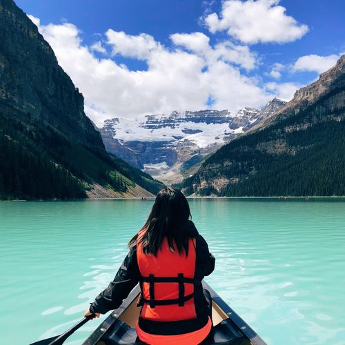 Rear view of woman on lake by mountain against sky