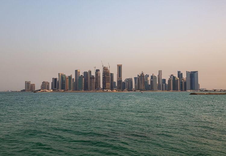 Sea by modern buildings against clear sky