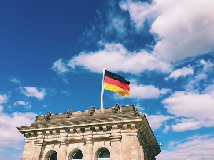 Low angle view of german flag on the reichstag against cloudy blue sky during sunny day