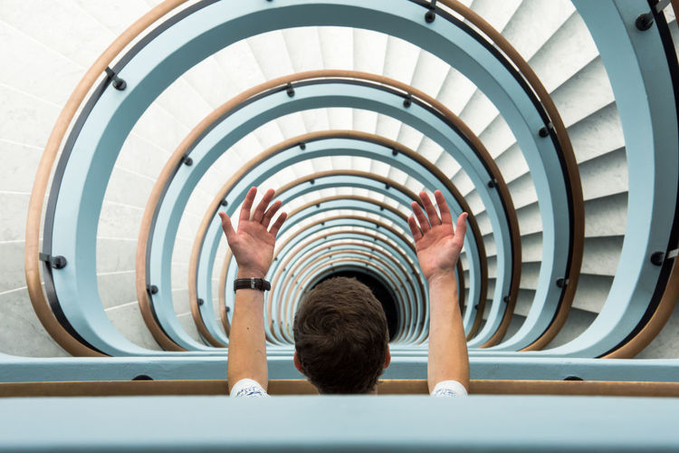 High angle view of man gesturing at spiral staircase