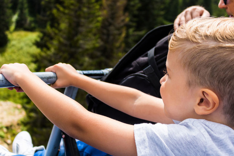 Small boy enjoying the ride on chairlift while having vacation with his dad.