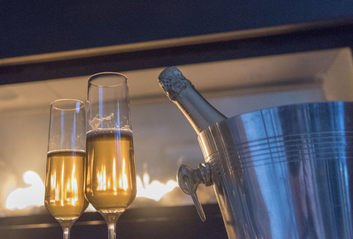 Champagne by the fireplace Alcohol Bubbles Celebration Champagne Cheers Couple Cozy Fireplace Flames Flutes Home Hotel Ice Bucket Interior Romantic Toast Travel Vacation Valentines Day Warm