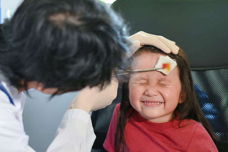 Doctor treating girl with injured head at clinic