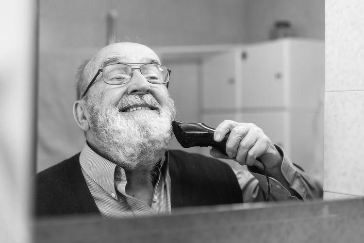 Reflection of senior man shaving in bathroom