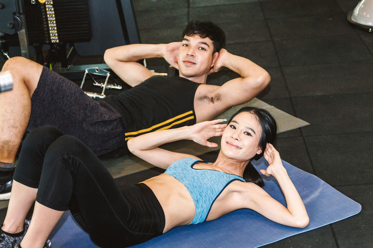 Portrait Of Young Man And Woman Exercising At Gym