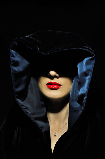 Close-Up Of Woman Wearing Hooded Shirt Against Black Background