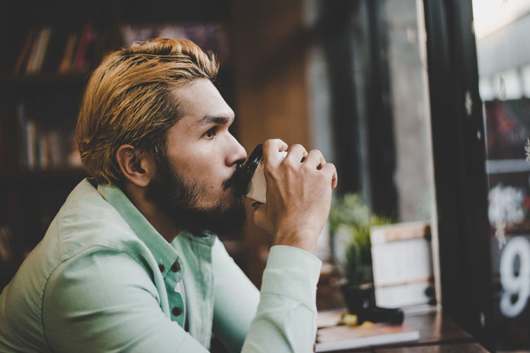 Man having coffee while sitting in cafe