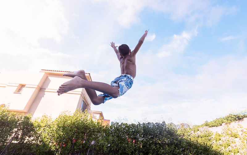 Low angle view of shirtless boy jumping against sky