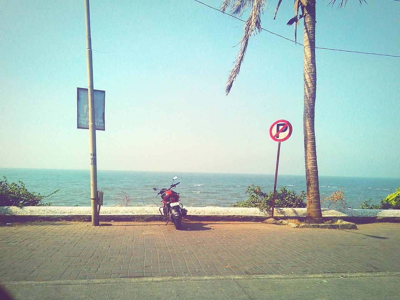 transportation, sea, bicycle, water, day, mode of transport, outdoors, land vehicle, sky, nature, road, one person, horizon over water, road sign, clear sky, real people, sitting, beauty in nature, tree, people