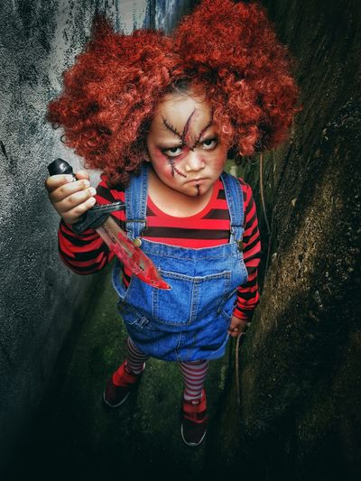 Portrait of girl with face paint and knife during halloween