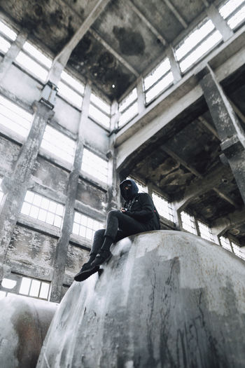 Low angle view of man sitting in abandoned building