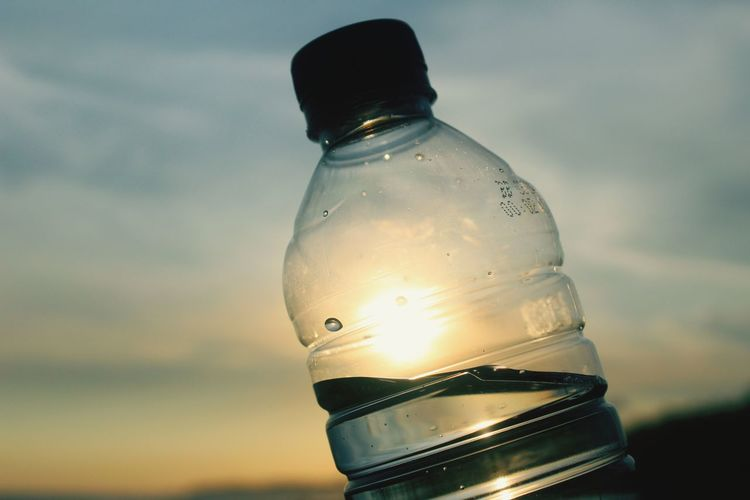 Close-up of water bottle against sky during sunset