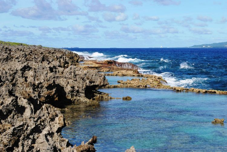 Scenic coastal views with clear blue waters in a tropical island Sea Water Sky Rock Scenics - Nature Beauty In Nature Rock - Object Horizon Over Water Horizon Rock Formation Land Solid Beach Nature Tranquil Scene Day Tranquility Cloud - Sky No People Outdoors Rocky Coastline Saipan Saipan Photos Northern Mariana Islands