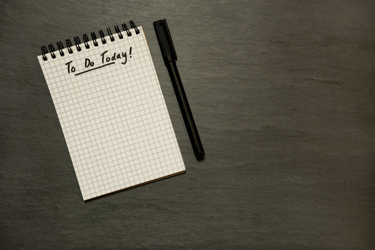 To do list on gridded spiral notepad and pen on slate table top - from above, minimal Business Goals Grid Schedule URGENT Black Clean Dark Background Directly Above Grey Lined Paper Minimal Note Pad Organised Page Paper Pen Planning Day Simple Life Slate Table Table Top To Do List Today