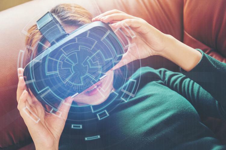 High Angle View Of Woman Enjoying Virtual Reality Simulator On Sofa
