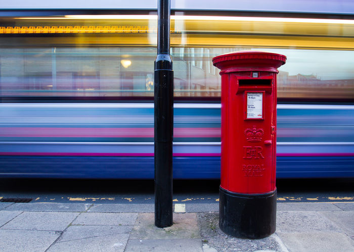 A red British Royal mail post box on the city streets with the motion blur of a bus caught in the background. City City Life City Life City Street Letterbox Motion Motion Blur No People Outdoors Post Postal Postbox Public Transport Red Red Royal Mail Royalmail Snail Mail Street Street Photography Streetphotography Transportation