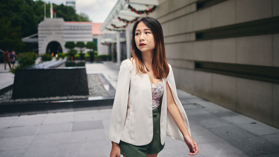 One Person Architecture Long Hair Hairstyle Young Adult Focus On Foreground Hair Casual Clothing Three Quarter Length Day Looking At Camera Portrait Women Young Women Real People Front View Adult Built Structure Beautiful Woman Outdoors Contemplation
