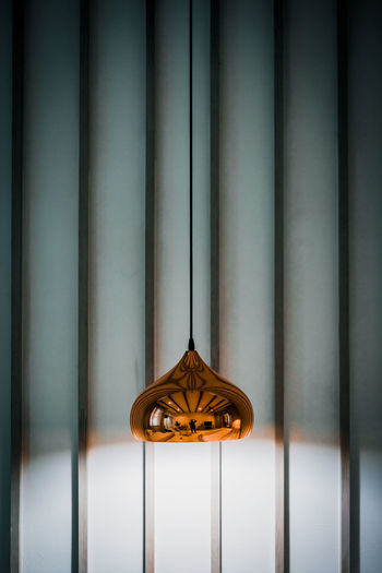 Close-up of illuminated lamp against wall at home