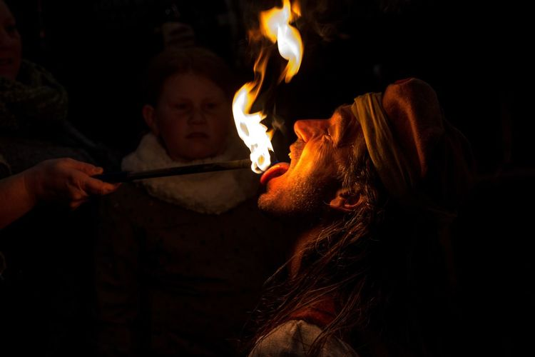Close-up of fire eater at night