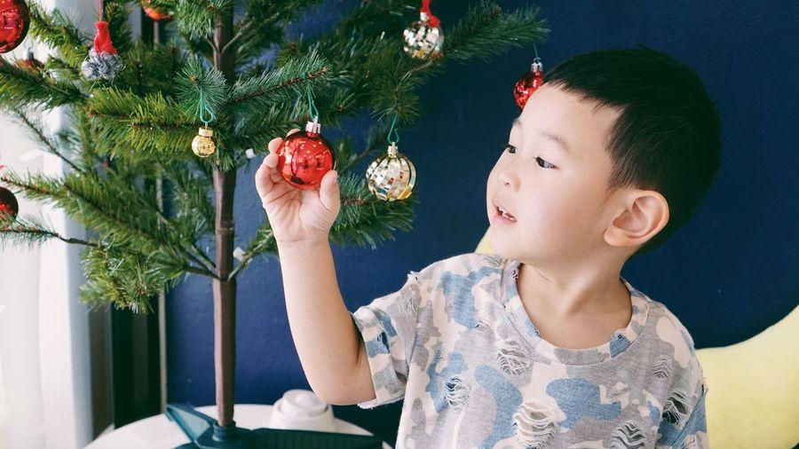 Full length of girl looking away at christmas tree