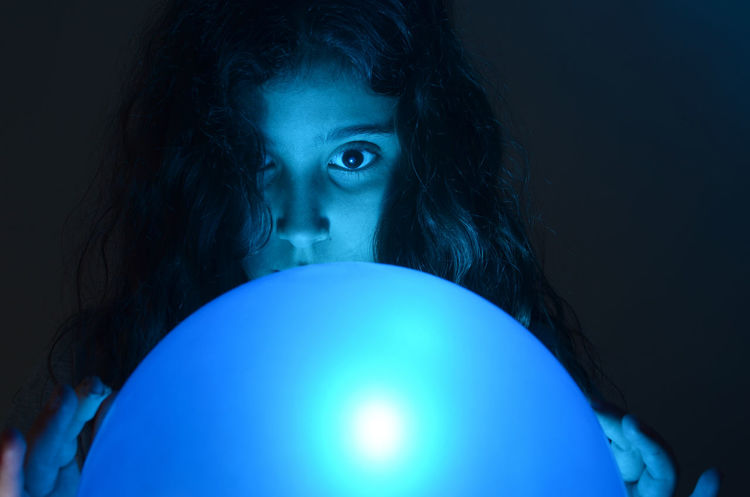 Portrait of young girl Ball Baloon Blue Closeup EyeEm Best Shots Eyes Face Fortune Telling Girl Illuminated Indoors  Lighting Equipment Mood People Portrait Sphere Spooky Studio Shot The Portraitist - 2017 EyeEm Awards