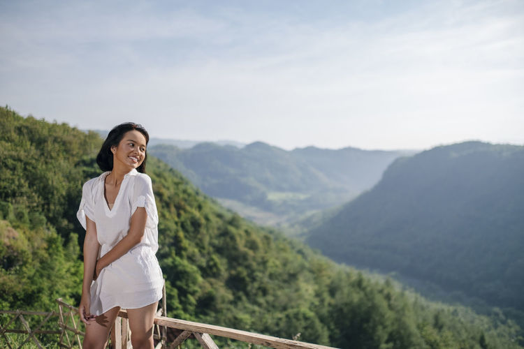 Smiling woman standing by railing against mountains and sky