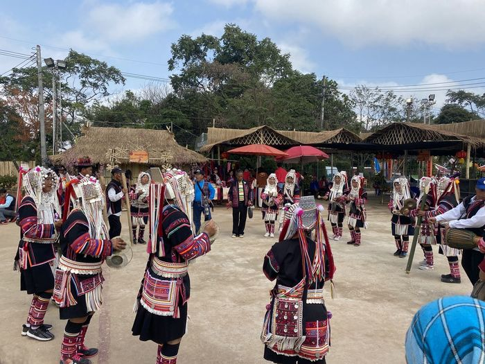 Group of people in traditional clothing against sky