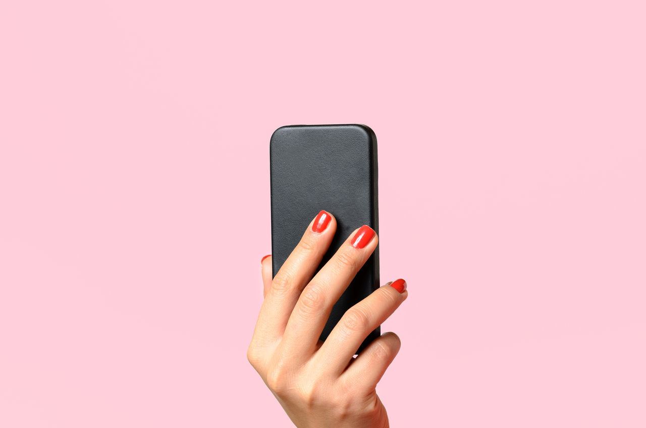 Cropped image of woman hand holding mobile phone against pink background