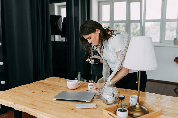 Woman photographer freelancer shoots content for business at home office