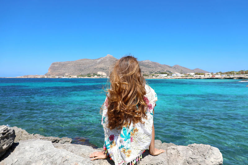 Rear view of woman looking at sea against clear blue sky