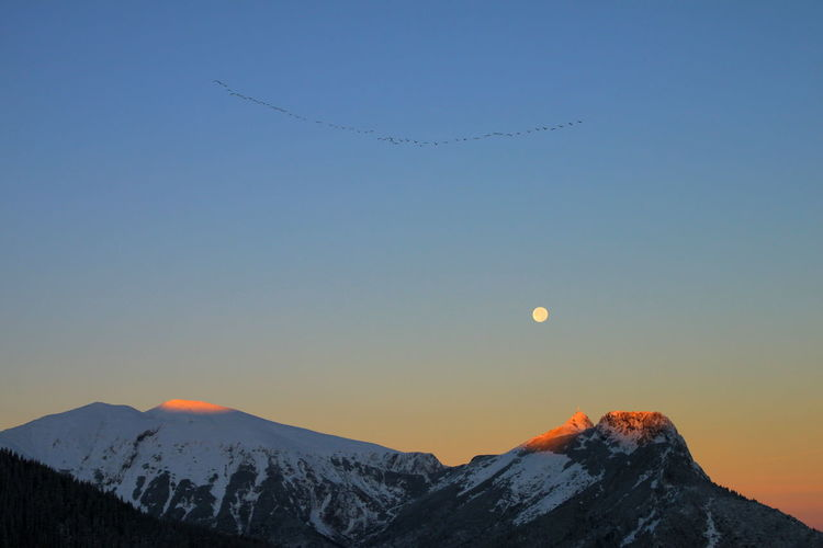 Scenic View Of Snowcapped Mountains Against Clear Sky During Sunrise