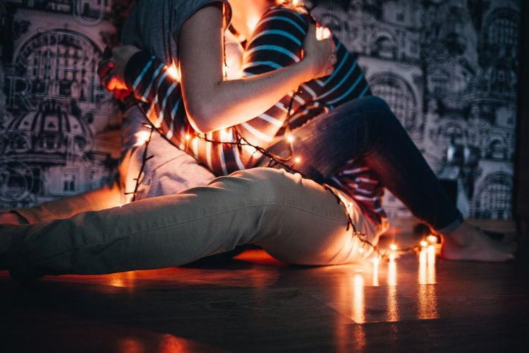 Low section of couple with illuminated string lights embracing at home