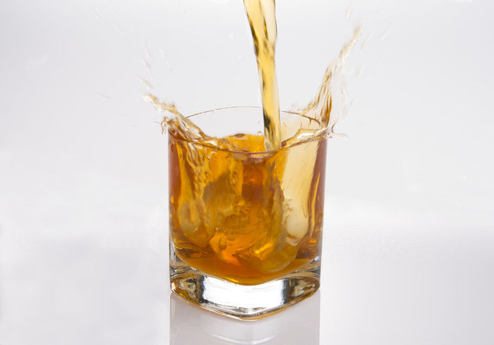 Splash in glass of scotch whiskey with ice cubes Abuse Alcohol Bar Brandy Celebration Cold Cube Food And Drink Liquid Lunch Luxurylifestyle  Restaurant Scotch Scotch Whisky Splash Studio Whiskey White Background