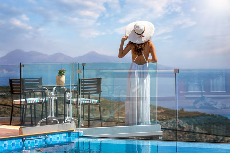 Rear view of woman standing by swimming pool against sky