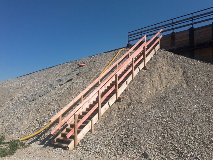 Low angle view of stairs against clear blue sky