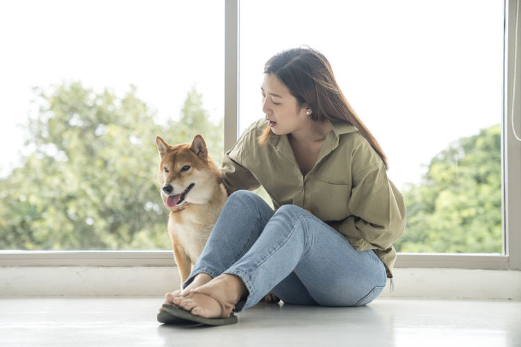 Woman with dog sitting against window