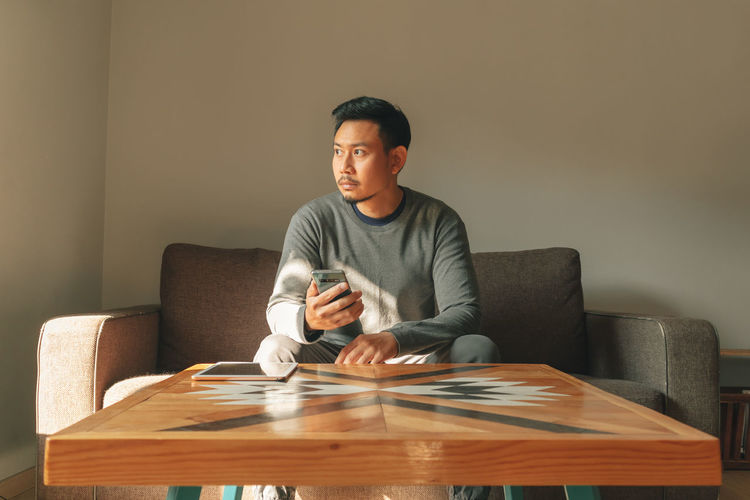 Young man sitting on table at home