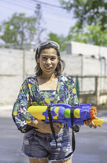 Portrait of smiling young woman holding squirt gun on road