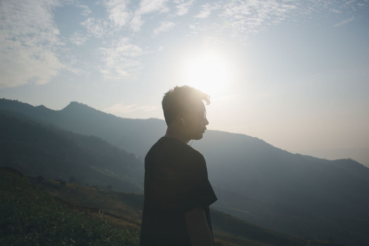Side view of man looking away standing against mountain