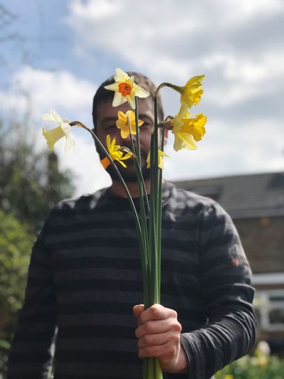 Low Angle View Of Man Holding Yellow Flowers Against Cloudy Sky
