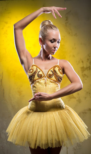 Lovely ballerina in yellow tutu posing over obsolete wall Adult Artist Ballerina Ballet Ballet Dancer Ballet Tutu Beautiful Woman Blonde Bodice Caucasian Choreography Dancer Female Girl Indoors  People Pirouette Pose Posing Professional Dancer Serious Studio Shot Woman